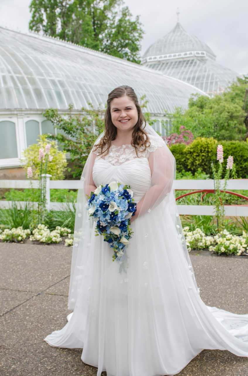 bride smiles with her blue cascade bouquet outside of phipps conservatory in pittsburgh