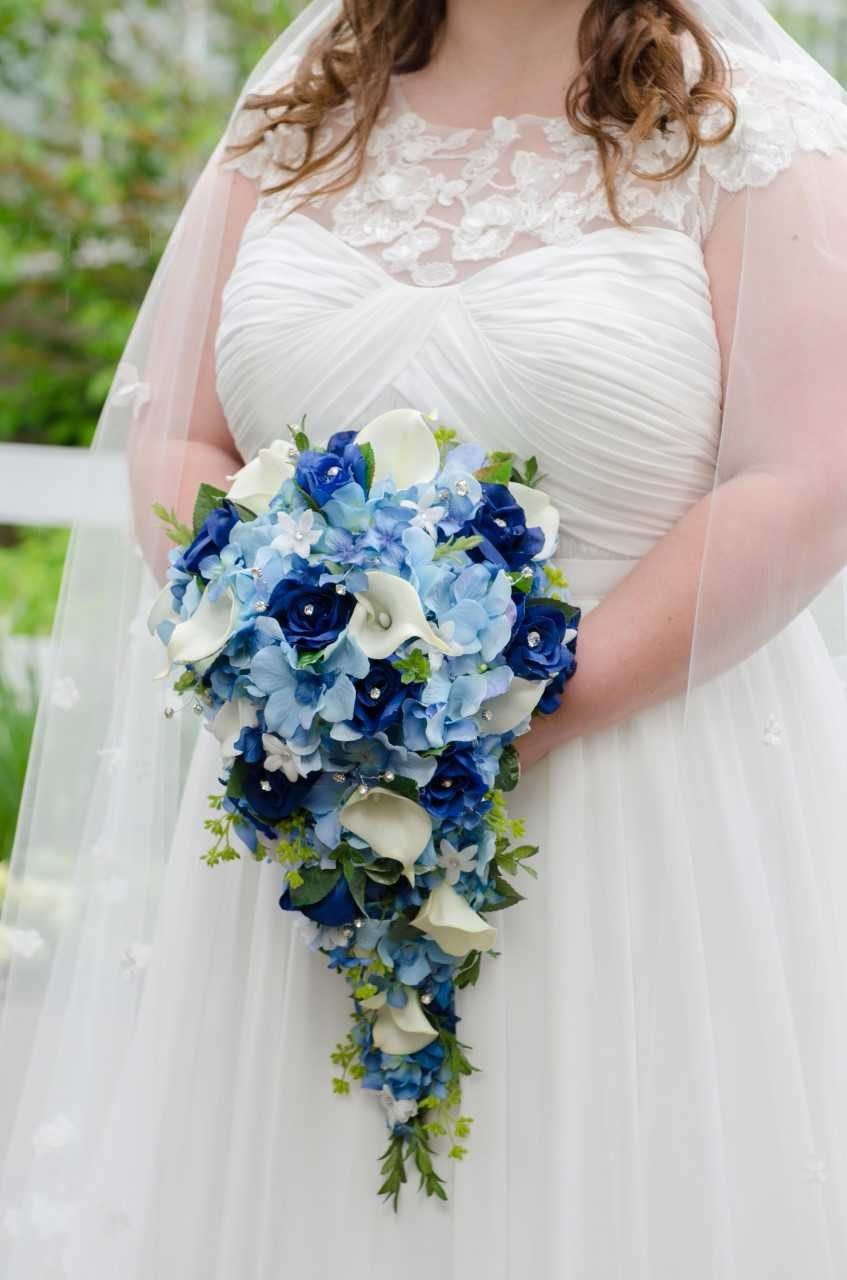 bride holding a blue cascade bouquet of roses hydrangeas and calla lilies