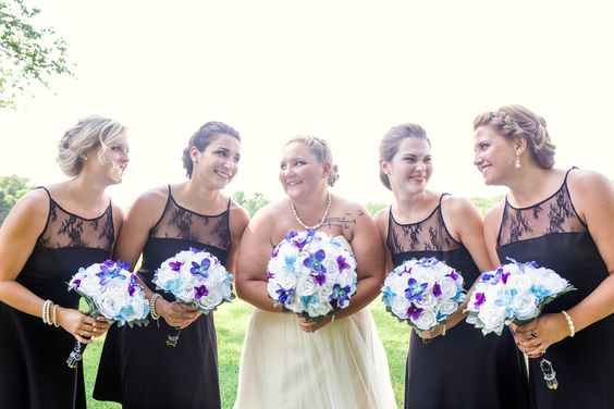 bride and bridesmaids holding wedding flowers at foggy mountain lodge
