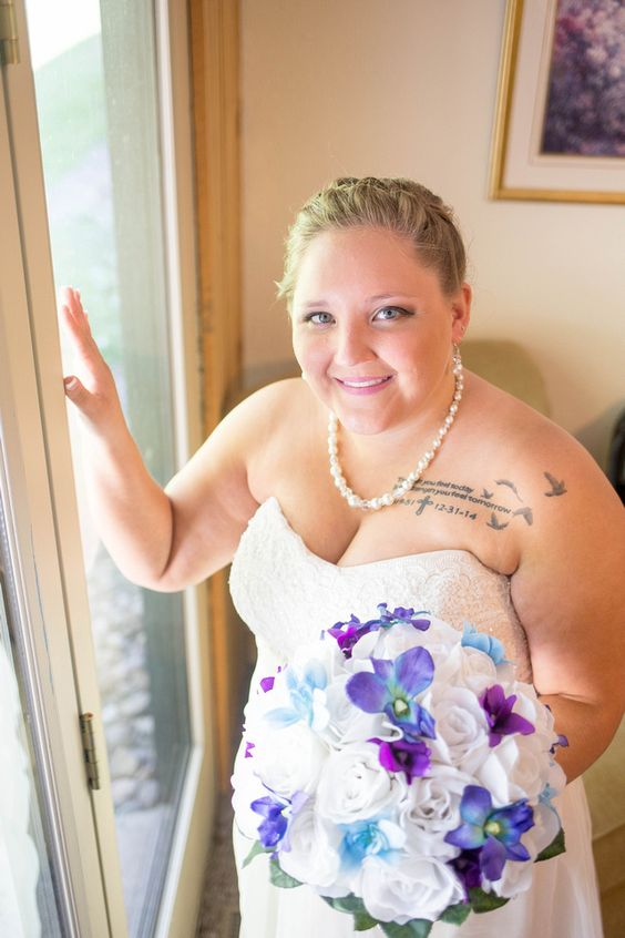 bride posed by window holding wedding bouquet at foggy mountain lodge