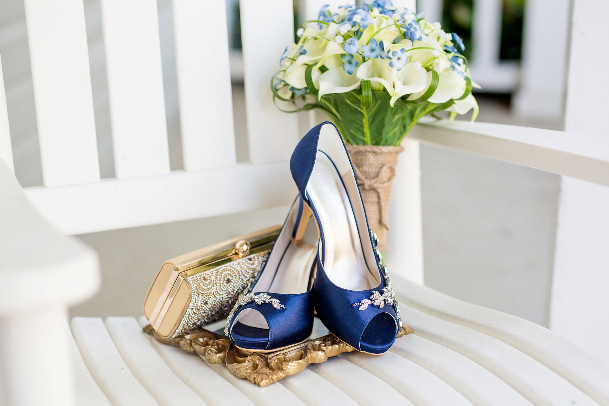 bride's calla lily bouquet and navy wedding shoes on a white rocking chair