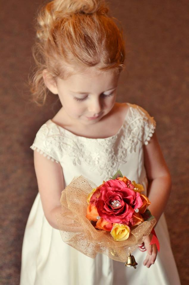 sweet flower girl admires her flower girl wand featuring a red rose