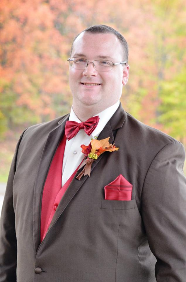 groom in chocolate brown tux with fall boutonniere