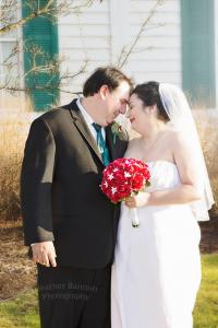 bride and groom outdoors with red rose bouquet