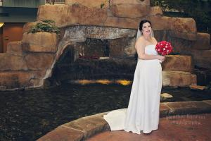 bride posing with red rose bouquet at embassy suites moon township